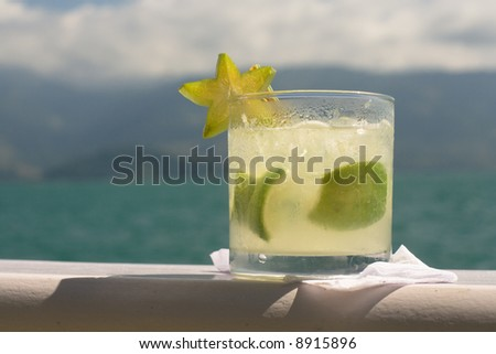 Caipirinha (cocktail) with star fruit garnish, with beautiful blue-green water and hills in the background. - stock photo