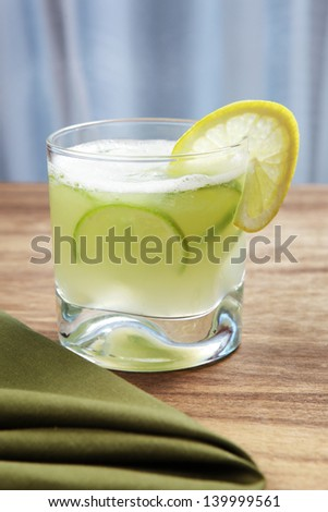 Caipirinha with fresh lime slices and ice - stock photo