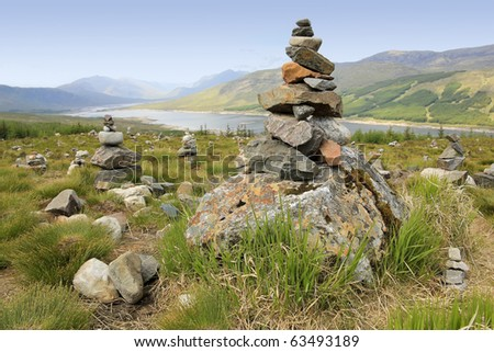 cairns or rock piles on the top of mountain overlooking loch in the highlands of scotland - stock photo