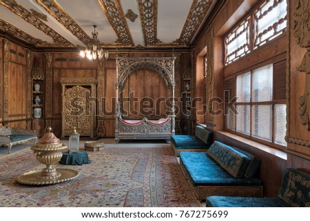 Cairo, Egypt - December 2, 2017: Manial Palace of Prince Mohammed Ali. Residence of prince's mother with golden ornate niche, silver bed, golden wardrobe, blue couches, ornate wooden wall and ceiling
