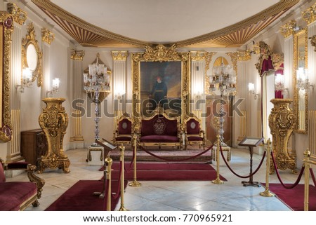 Cairo, Egypt - December 2, 2017: Throne Hall at Manial Palace of Prince Mohammed Ali Tewfik with gold plated red armchairs, antique floor lamps, ornate ceiling and red carpets