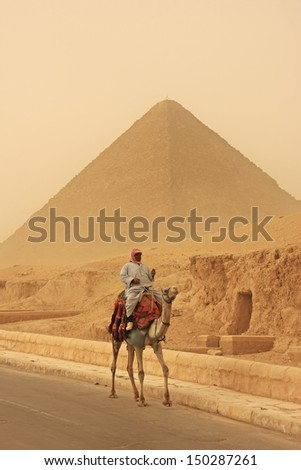 CAIRO, EGYPT-DECEMBER 11: Unidentified man rides camel near Pyramid of Khufu on December 11, 2010 in Egypt. Great Pyramids are the oldest of the ancient Wonders and the only one still in existence. - stock photo