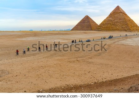 Cairo, Egypt - January 9, 2015: Pyramids in Giza and people riding bicycles.