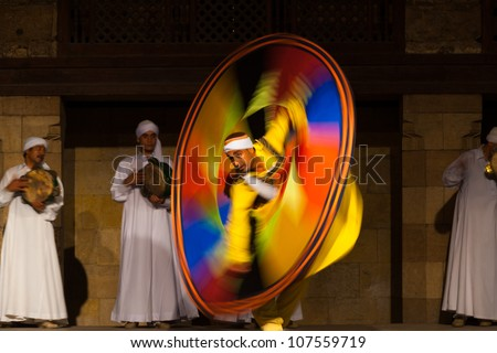 CAIRO, EGYPT - JULY 3: An Egyptian Sufi dancer in yellow spins during a whirling dervish at an open air courtyard performance, a famous tourist attraction in Cairo, Egypt on July 3, 2010 - stock photo