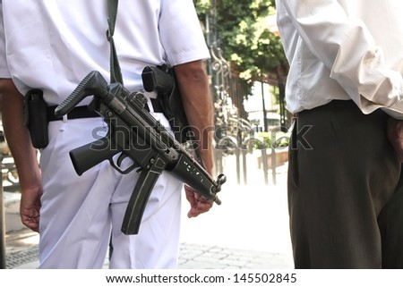 CAIRO, EGYPT-JUN 15: A tourist police with submachine guns guards at the entrance of Egyptian Museum on June 15, 2011. The museum was invaded during Egyptian revolution on Jan 2011. Cairo. - stock photo