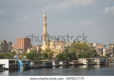 CAIRO, EGYPT - NOVEMBER 19, 2011: Riverbank in Cairo, Egypt, with mosque, residential houses and other city buildings in the background. Cairo is the capital city of Egypt. - stock photo
