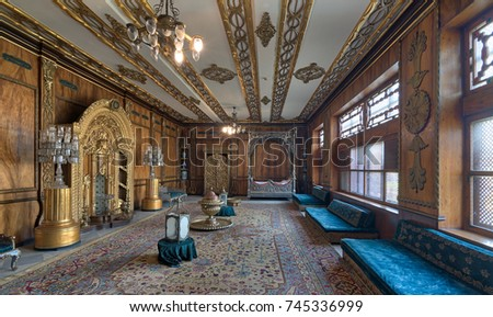 Cairo, Egypt - October 21 2017: Manial Palace of Prince Mohamed Ali. Residence of prince's mother with golden ornate niche, silver bed, golden wardrobe, blue couches, ornate wooden wall and ceiling