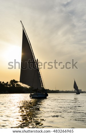 "Cairo, Egypt - Traditional pleasure boat ""Felluca"" silhouette at sunset in Nile River"