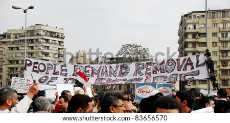 CAIRO - FEB 1: A large group of Egyptian anti-government protesters attach a big banner to light poles in Cairo, Egypt's central Tahrir Square on  Feb 1, 2011. - stock photo