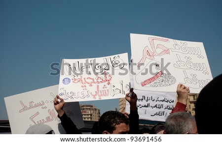 CAIRO – JAN 25: Egyptians hold signs calling for the fall of the military council in Cairo, Egypt on January 25, 2012 - stock photo