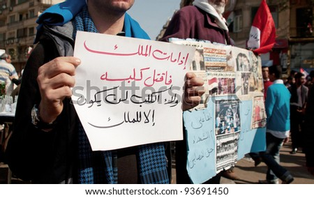 "CAIRO - JAN 25: Protester holds a sign on anniversary of Egypt's uprising in Tahrir Square. says ""If the king dies, kill his dog. It won't be loyal to someone but the King"" Cairo, Egypt. Jan 25, 2012 - stock photo"