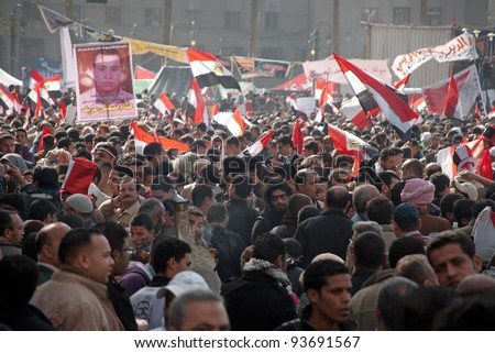 CAIRO – JAN 25: Thousands of Egyptians gather in Tahrir Square hold flags, pictures of martyrs, signs against military council on first anniversary of Egypt's uprising in Cairo, Egypt on January 25, 2012 - stock photo