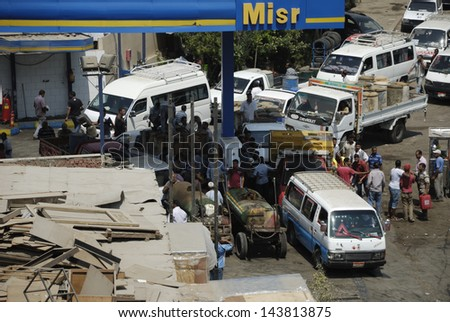 CAIRO - JUNE 27: Crowds in MISR petroleum station, where vehicles and unidentified people hold empty tanks to get 80 octane fuel in Maadi, Cairo, Egypt. June 27, 2013