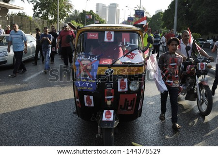 CAIRO - JUNE 30: Demonstration signs and stickers against the President Morsi on a motor tricycle (Toktok) in el-Tahrir Street on June 30, 2013 in Cairo, Egypt - stock photo
