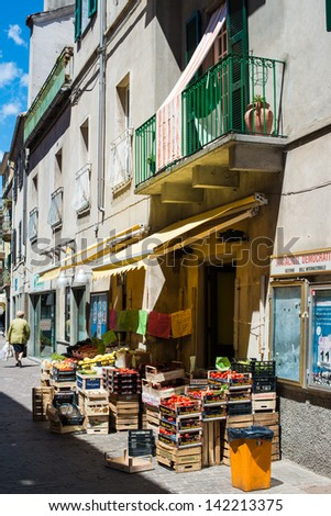 CAIRO MONTENOTTE, ITALY - MAY 24, 2013: Freshly harvested fruits and vegetables being sold in front of a small greengrocer store in bright sunlight on May 24, 2013 in Cairo Montenotte, Italy. - stock photo
