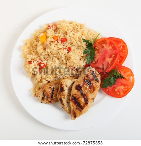 Cajun rice and chicken with a sliced tomato seen from above - stock photo