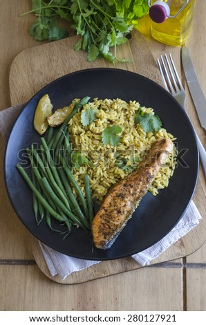 Cajun-style salmon with pilau rice and green beans - stock photo