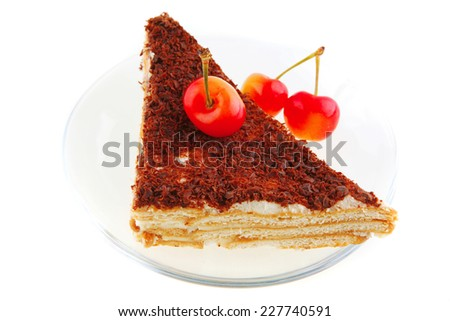 cake and cherry on transparent saucer over white - stock photo