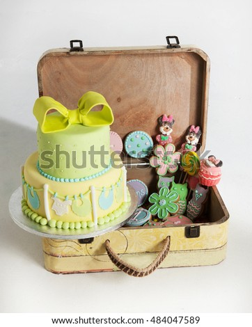 cake and others candies for baptism day on a vintage suitcase