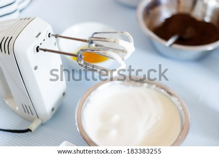 Cake batter and mixer on a table top.  - stock photo