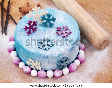 cake decorated with fondant on the wooden board - stock photo