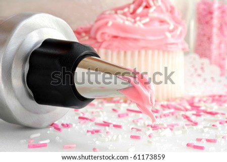 Cake decorating still life with fresh strawberry frosting dripping from pastry tip and cupcakes with sprinkles in background.  Macro with shallow dof. - stock photo