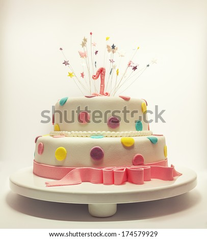 Cake for first birthday, number one made of sugar on top with stars around it.  - stock photo