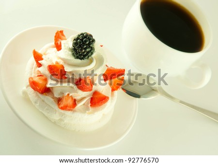 Cake from cream, strawberries and blackberries, a cup of fragrant coffee