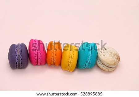Cake macaron or macaroon on pink background from above, colorful almond cookies, pastel colors, vintage card, top view