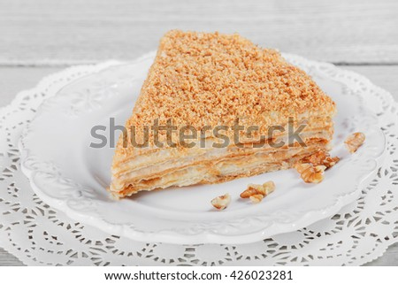 Cake Napoleon with sour cream and walnuts on plate, on a light wooden background. Selective focus - stock photo