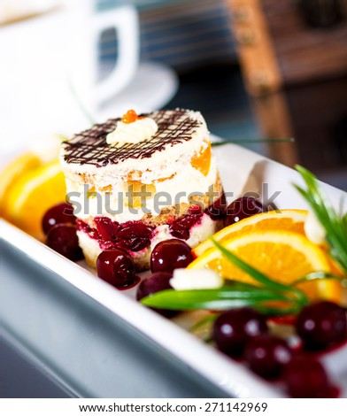 Cake on a white plate with fresh fruit - stock photo