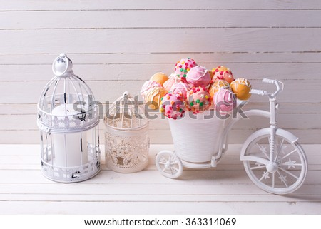 Cake pops  in decorative bicycle and candles  on white wooden background. Selective focus.