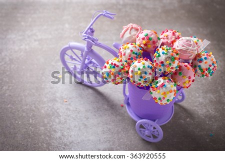 Cake pops  in decorative bicycle on grey slate  background. Selective focus.  - stock photo