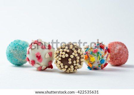 cake pops isolated lying on white table. - stock photo