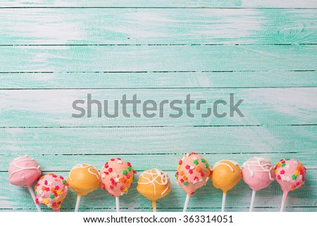 Cake pops on turquoise  painted wooden background. Selective focus.Place for text. - stock photo