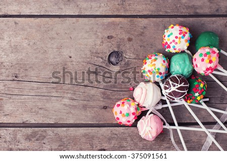 Cake pops on  vintage wooden background. Selective focus.Place for text. Top view.