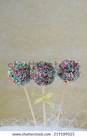 Cake pops with chocolate and sprinkles on golden background - stock photo