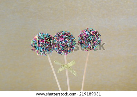 Cake pops with sprinkles on golden background - stock photo