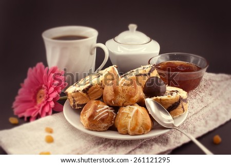 Cake roll and eclair on plate with coffee on dark background, selective focus - stock photo