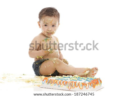 Cake smash.  Adorable baby boy covered in cake and frosting.  Isolated on white with room for your text. - stock photo