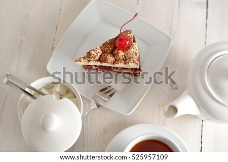 cake, tea Cup and sugar bowl on a wooden countertop