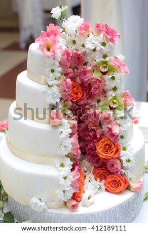 Cake traditional anniversary birthday wedding four-layer beautiful delicious sweet dessert decorated with butter-cream roses on blurred background