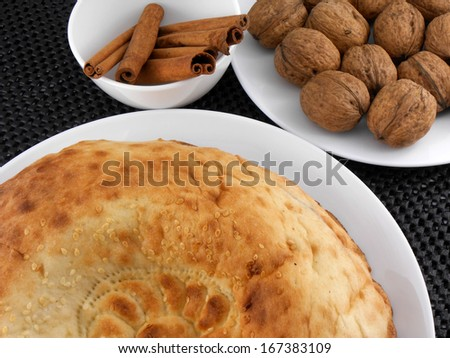 cake, walnut and cinnamon on white plate - stock photo