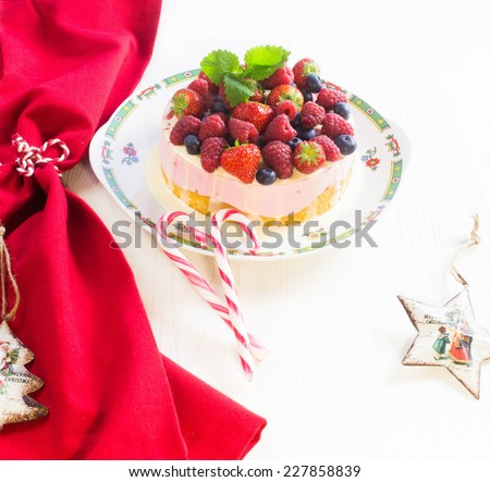 Cake with Berries and christmas decorations on white wooden background - stock photo