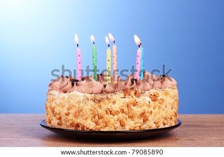 Cake with candles on blue background