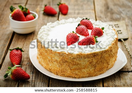 cake with cream and strawberries on a dark wood background. tinting. selective focus - stock photo
