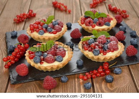 Cake with custard and berries on a brown background - stock photo