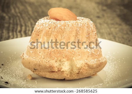 Cake with dry apricot and sugar powder on the white plate on wooden table.Toned.  Selective focus. - stock photo