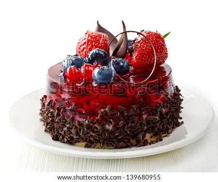 cake with fresh berries and chocolate on white plate - stock photo