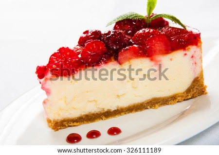 Cake with fresh culinary herbs strawberries on white plate.